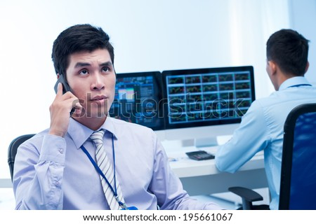 Young broker talking on the phone while his colleague is analyzing market - stock photo