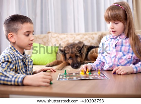 young brother and sister playing at home,German Shepherd dog in the background watching - stock photo