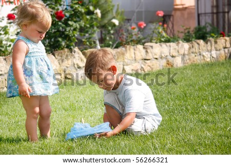 young brother and sister playing in park - stock photo