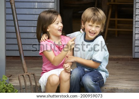 Young brother and sister sitting on veranda - stock photo