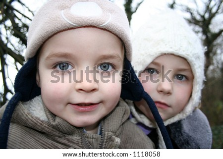 Young brother and sister walking in the winter. - stock photo