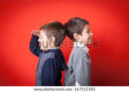 Young brothers funny portrait against red background. - stock photo