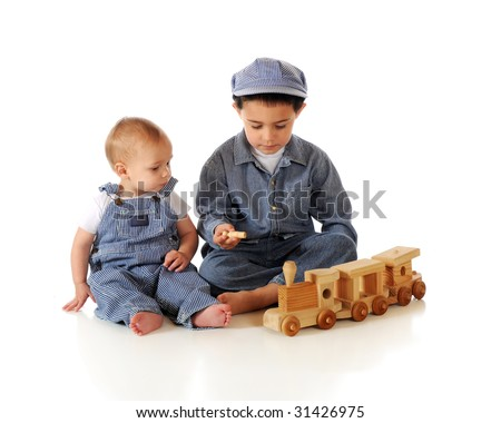 Young brothers in striped denim work clothes and an engineer's cap playing with a wooden toy train.  Isolated on white. - stock photo