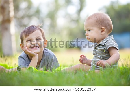 Young brothers playing on grass in a park - stock photo