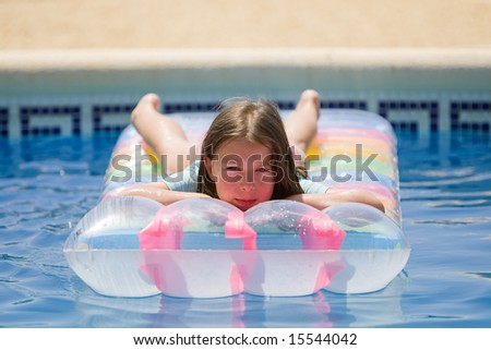 Young Brown Haired Child on Swimming Pool Air Bed - stock photo