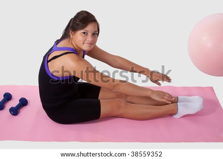Young brunette aboriginal teen girl wearing workout attire sitting on pink mat reaching for toes - stock photo