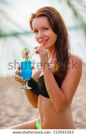 young brunette beautiful woman resting on sand beach, she is drinking blue cocktail - stock photo