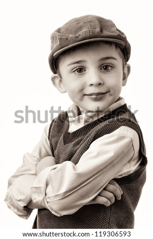 Young brunette caucasian boy with vest with arms crossed wearing flat cap - stock photo