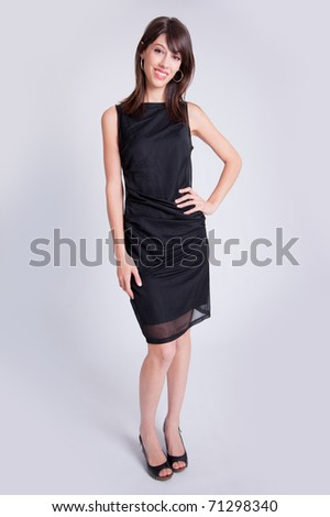 Young brunette dressed up in a little black dress and high heels - stock photo