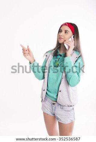 Young brunette female student standing and calls the smartphone. Beautiful young backpacker - stock photo