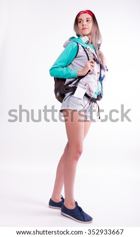 Young brunette female student standing and listening to music from your device. Beautiful young backpacker - stock photo