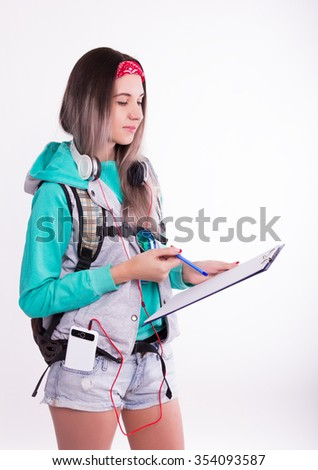 Young brunette female student standing and listening to music from your device. Beautiful young backpacker writing down some notes. - stock photo