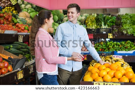 Young brunette girl and boyfriend buying citruses in grocery store - stock photo
