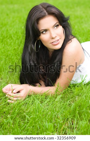 Young brunette girl relaxing on green grass - stock photo