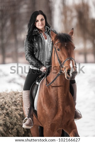 Young brunette girl riding horse - stock photo