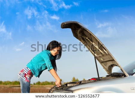 young brunette girl with a broken car with open hood - stock photo