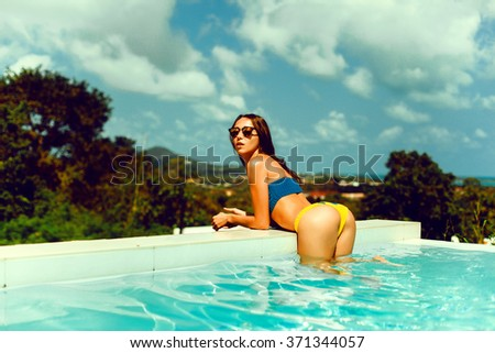 young brunette girl with makeup long legs poses in blue swimsuit in a pool of blue water, luxury Villa with sea views, palm trees, luxury,VIP area,beautiful tan body,tanned skin, sunglasses,posing ass - stock photo
