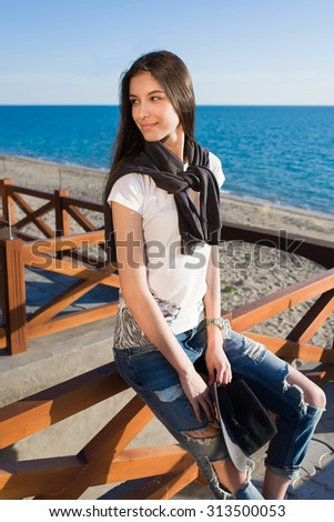 Young brunette hair female in trendy clothes enjoying beautiful sunny afternoon while sitting on the beach against the sea, stylish hipster girl resting on the beach after evening promenade - stock photo