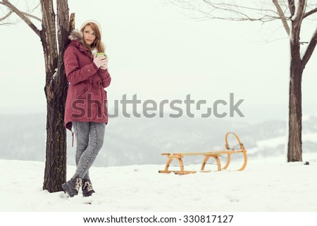 Young brunette holding a cup of hot tea and enjoying the cold winter magic moments - stock photo