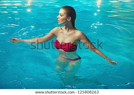 Young brunette in a swimming pool - stock photo