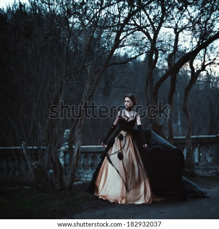 Young brunette in an ancient mystical surroundings. Grain added. Color as a creative solution to author - stock photo