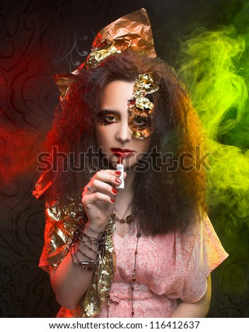 Young brunette in creative image posing with color smoke - stock photo