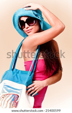 young brunette in pink summer dress, wearing hat, sunglasses and beach bag - stock photo