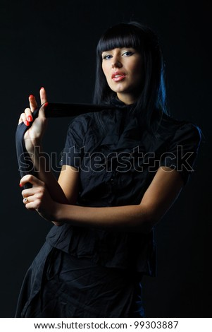 Young brunette lady in black dress posing on dark background - stock photo