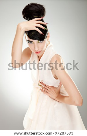 Young brunette lady in dress posing on grey background - stock photo