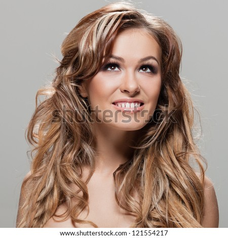 Young brunette lady with a beautiful hair on gray background - stock photo