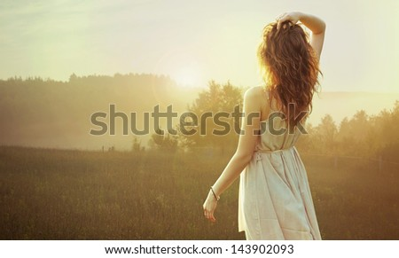 Young brunette looking at sunrise - stock photo