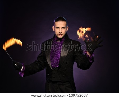 Young brunette magician in stage costume performing flame tricks - stock photo