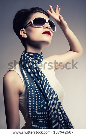 young brunette model wearing a sunglasses and a scarf posing on gray background - stock photo