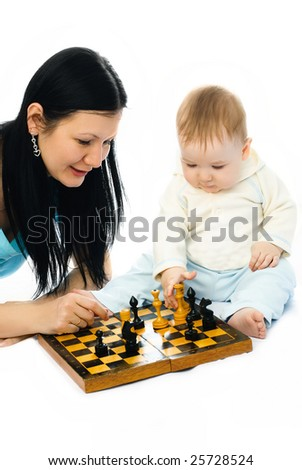 young brunette mother and her ten months old baby playing chess on the floor - stock photo