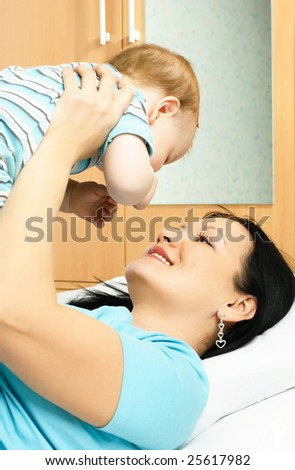 young brunette mother lies on the bed with her ten months old baby - stock photo