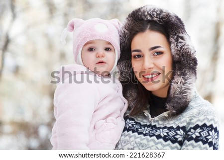 Young brunette mother with her daughter outdoors. Winter time - stock photo