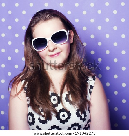 Young brunette pretty teenager girl posing over dots background, wearing sunglasses. - stock photo