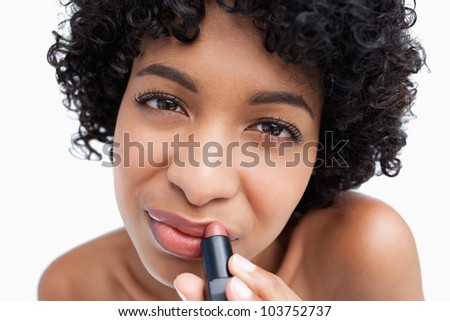 Young brunette putting pink lipstick on her lips against a white background - stock photo