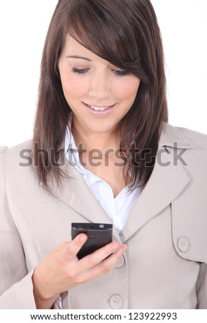 Young brunette sending message with mobile phone - stock photo