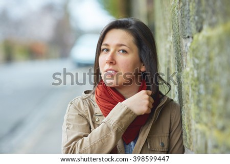 Young brunette shoot against stone wall, wear red scarf and khaki jacket - stock photo