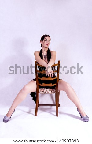 young brunette sitting on chair - stock photo