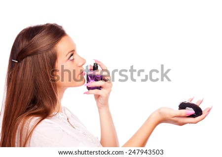 Young brunette smelling perfume bottle, isolated on white - stock photo