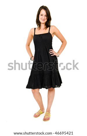 Young brunette standing with her hands on her hips looking defiantly - stock photo