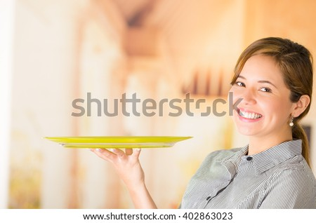 Young brunette waitress wearing uniform with friendly smile, holding up tray using one hand, posing happily for camera - stock photo