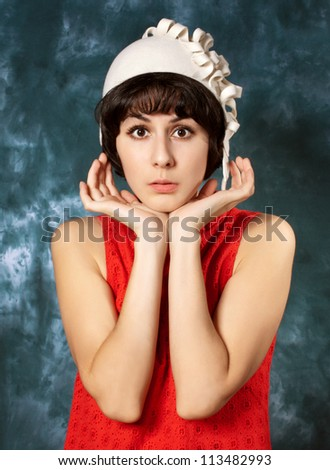 young brunette wearing red dress and  white  felt hat  - stock photo