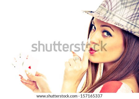 Young brunette with hat, holding four aces and showing shush sign with index finger on her lips - studio shot - stock photo