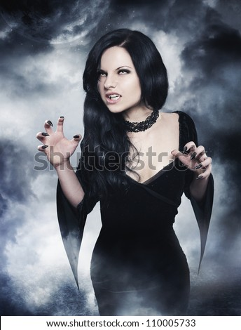 Young brunette woman as sexy vampire on  night background - stock photo