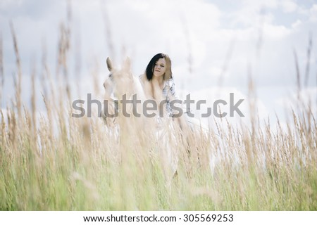 Young brunette woman enjoying summer freedom, riding her beautiful white horse in the sunny field - stock photo