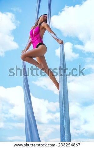 Young brunette woman gymnast on blue sky background. - stock photo