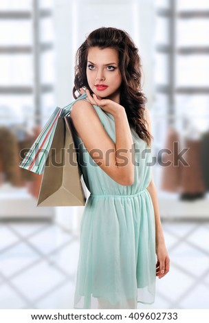 Young brunette woman holding shopping bags  in clothing store - stock photo